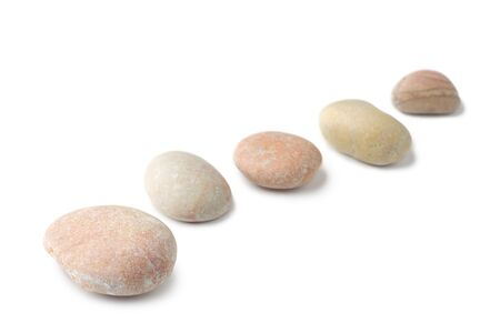 Row of pebbles isolated on white background photo