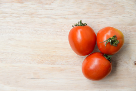 Tomatoes on wooden table background