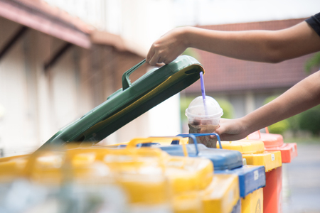 children hand throwing empty plastic bottle into the trash.saving environment by throwing plastic jung in to the recycle bin or garbage