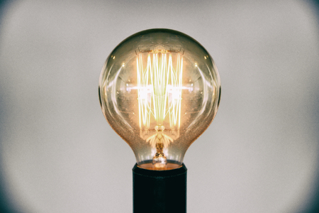 Decorative antique edison style light bulb.Beautiful retro luxury light lamp decor glowing selective focus film grain style effect.