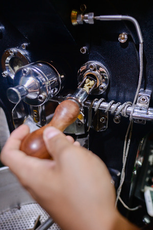 Checking roasted coffee beans.a mans hands quality control checking aromatic coffee beans over a modern machine used for roasting beans.selective focus Stock Photo