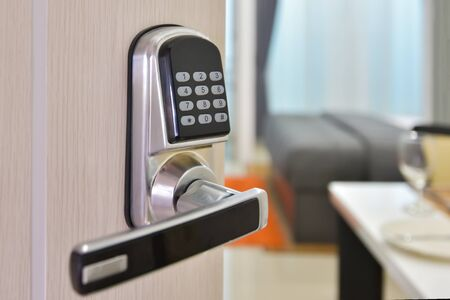 Máquina de sistema eletrônico de controle de acesso de porta com porta de senha de número ... Metade abriu o puxador da porta closeup, entrada para uma sala de estar. Fechadura da porta com número de chaves.