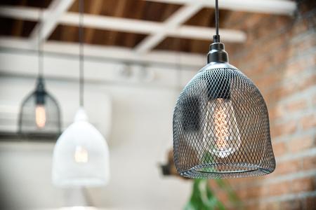ヴィンテージ喫茶店インテリア背景にぶら下がっている現代の電球 写真素材