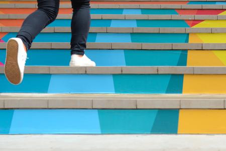Unterer Teil der Jugendlichen im zufälligen Schuh gehend herauf bunte Treppe im Freien, erfolgreiches Konzept des Jugendlebensstils Standard-Bild