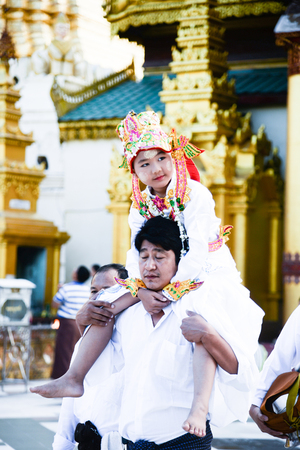 17 December 2016 young myanmar childern in traditional cloth ride the neck of his cousin walking around the shwedagon pagoda in buddhism ordained ceramony in yangon,myanmar