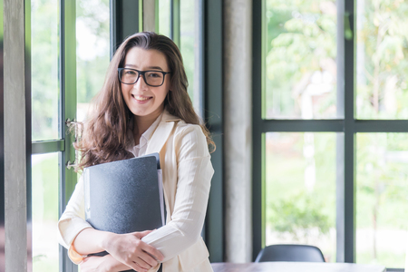 Portrait of young businesswoman smileing and holding document, . Success in business, job and education concept