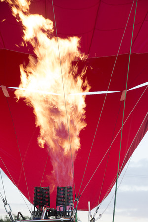 inflames fire and inflates the balloon.Detail of a large hot air balloon being inflated for its initial flight.