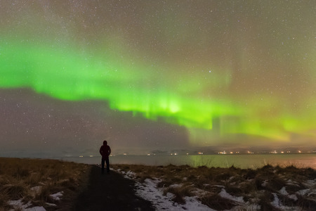 Aurora Borealis (Northern Lights) phenomenon in winter.Photographer standing under Aurora Polaris solar storm above his head at night in iceland Foto de archivo