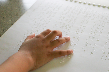 Braille is the font for the blind, invented by Louis Braille. The French blind teacher is a small convex dot in a six-point box, which is arranged alternately into code. Fine letters or mathematical symbols, science, music notes, etc. Writing using a slate and a stylus. Printing using a printer called a Brailler Stock Photo