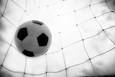 Success and win concept, Soccer ball in a net in bright background black and white with grain effect.