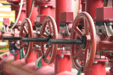 Red valves on metal pipe. Valve is a device that regulates, directs or controls the flow of a fluid like gases, liquids by opening, closing, or partially obstructing various passageways. Banco de Imagens - 117428299