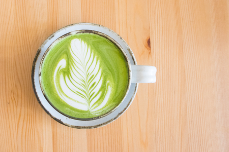 Matcha green tea latte in a cup on wooden table background.Hot Matcha coffee latte with beautiful milk foam latte art texture. Reklamní fotografie