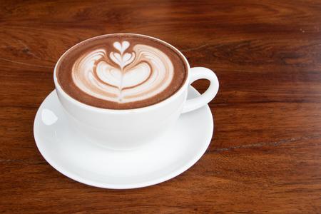 coffee cup latte art on wooden table.hot drink coffee with milk froth for breakfast.heart shape art foam texture top view. Reklamní fotografie