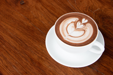 coffee cup latte art on wooden table.hot drink coffee with milk froth for breakfast.heart shape art foam texture top view. Stock Photo