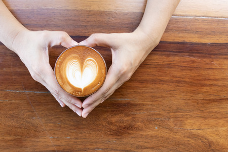 Coffee cup with latte art foam on wood table in coffee shop with copy space.Coffee is one of the most popular beverages.Improve Energy Levels and Burn Fat