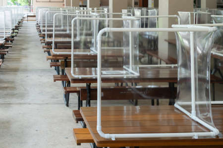 Preventing the spread of Covid-19 coronavirus in schools and universities by using plastic sheets divide the area in the cafeteria for social distance and new normal life policy in Thailand Stockfoto