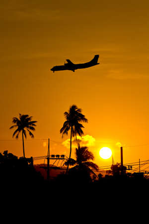 Silhouette landing plane at sunset