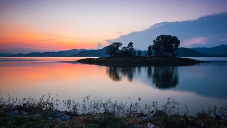 Small island at reservoir of dam after sunset photo