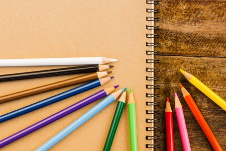 Gray notebook with colorful pencils on the wooden table photo