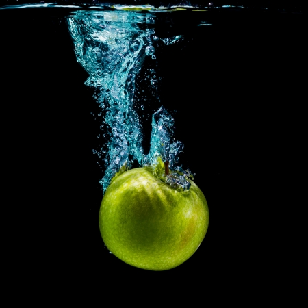 Green apple with splashing water on a black background