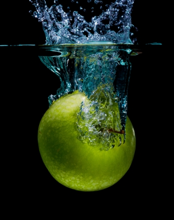 Green apple with splashing water on a black background photo