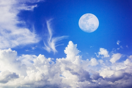 Moon on Blue Sky with white fluffy clouds Stock Photo