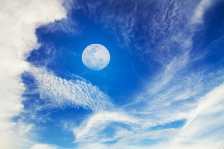 Moon on Blue Sky with white fluffy clouds photo