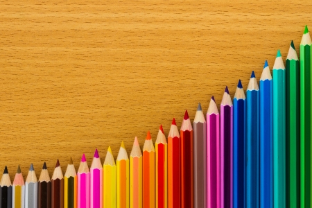 line of colored pencils on wooden background photo