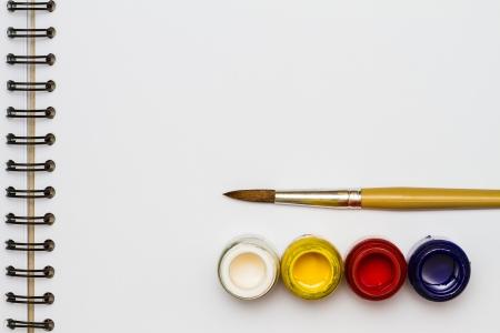 art book: Cepillos de pintura con cubos de pintura abiertos en el libro de dibujo