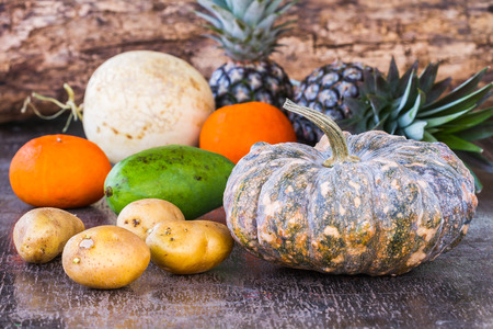 Pumpkins and fruits on wooden table photo