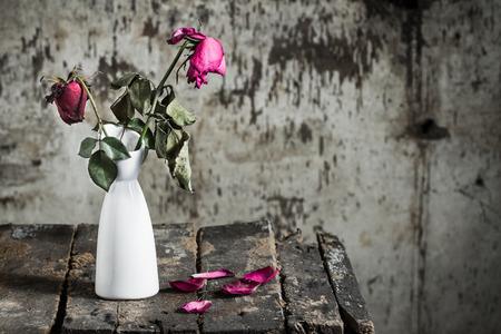 rosas amarillas: Rosas marchitas en florero en de madera viejo