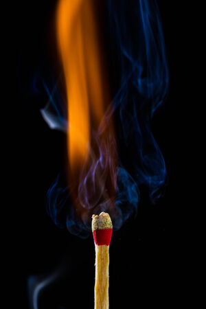 match head: Burning matchstick on black background