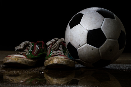 Dirty sneakers with soccer ball on black background photo