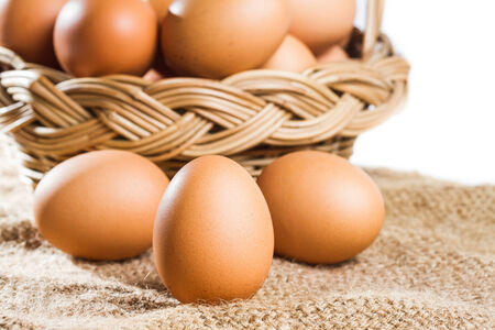 Close up fresh egg on brown burlap and basket photo