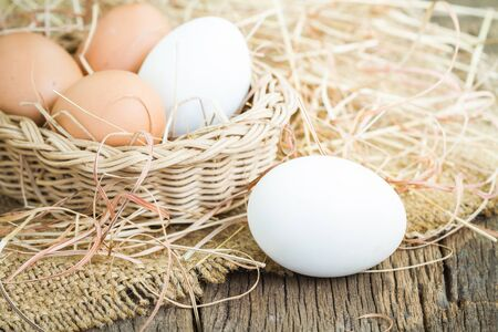 Close up of white fresh egg on basket with brown burlap on wooden floor photo