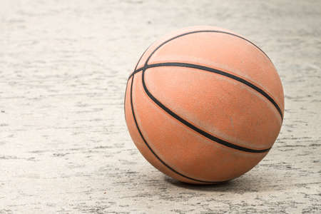 Old basketball on street background