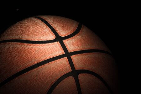 college basketball: Close up of old basketball on black background Stock Photo