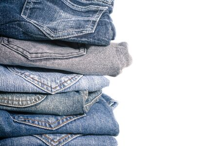 trouser: Close up of many jeans trouser stack on white background Stock Photo