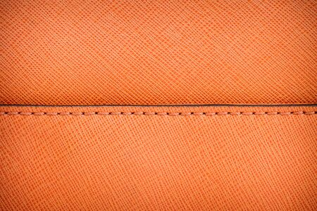 Orange textured leather background with stitch
