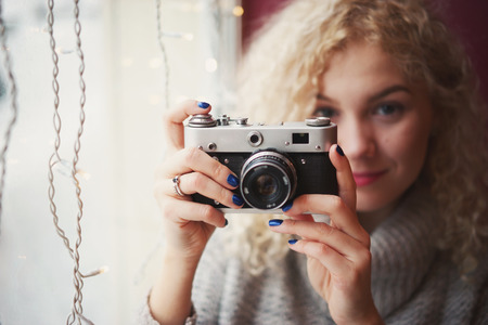 outside shooting: Young blond curly female in warm sweater with old film camera smiling and shooting a photo in the cafe, winter city outside the window
