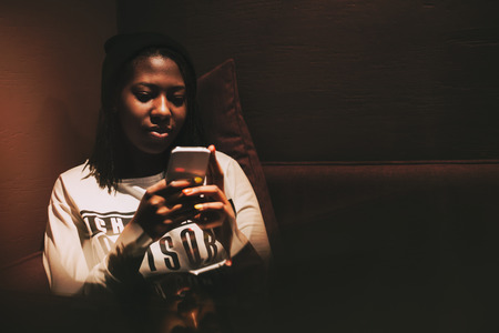 long sleeve shirt: Smiling young happy black african american girl sitting on a sofa in dark cafe at nighttime, wearing a hat and long sleeve shirt, using smartphone, vintage color filter Stock Photo