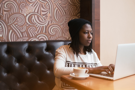 long sleeve shirt: Young black african american girl sitting on a leather sofa in a cafe at daytime, wearing a hat and long sleeve shirt, working on laptop and drinking coffee, nail art, vintage color filter Stock Photo