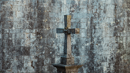 rood: Tombstone in the form of a Catholic cross. Gray moss-covered stone. On the background of a stone wall, Girona, Spain