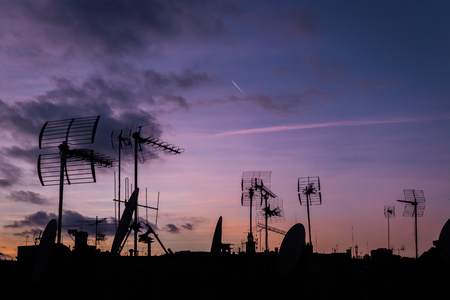Lilac sunset and a lot of silhouettes of roofs with antennas in Barcelona. Cloudy night, the plane trace in the sky Stock Photo