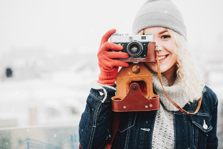 Young blond curly smiling female in warm clothes with retro film camera shooting a photo on the background of winter city, snow