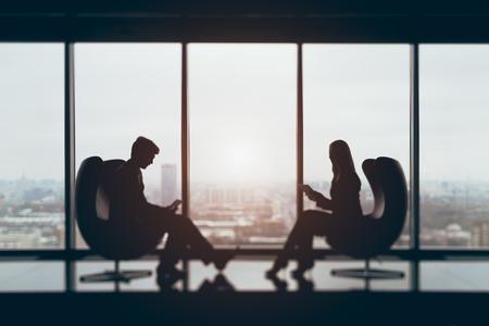 Echte Tilt-Shift-Dreharbeiten von Geschäftsmann und Geschäftsfrau vor einander sitzen mit ihren Gadgets in der zeitgenössischen Büro-Interieur, verschwommene Blick von oben auf Winter Stadt im Hintergrund