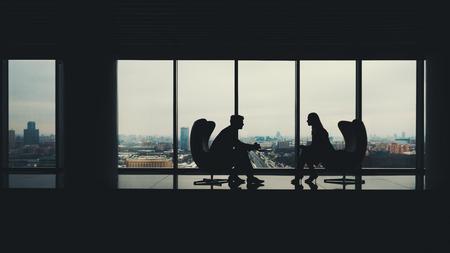 Sagome di due uomini d'affari uomo e donna seduta su poltrone in ufficio interno, uomo che mostra informazioni sullo schermo del suo computer portatile al suo collega, enormi finestre con paesaggio urbano invernale al di fuori