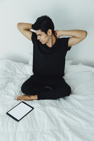 Young handsome attractive brazilian male in black t-shirt and tights stretching his arms sitting on bed after sleeping in the morning, mock up of digital tablet with white screen laying near him