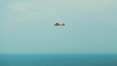 Orange one engine prop plane with teal stripes flying over the misty ocean in Rio de Janeiro, Brazil, bright sunny day with clear sky