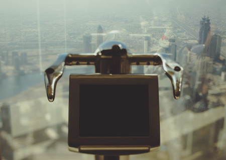 enlarger: Tilt shift shooting of electronic telescope in front of window of Dubai skyscraper with top view of cityscape on summer day